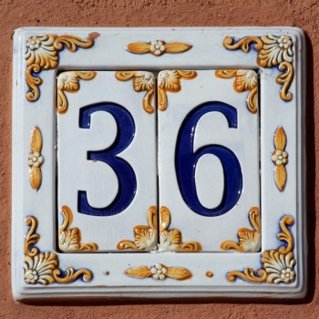 closeup of decorated house number digits sign on the wall